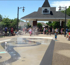 Kids playing on a large splashpad with jets of water shooting from the ground